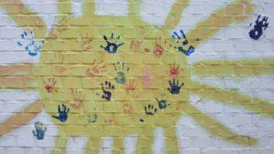 gemalte Sonne mit Abdrücken von Kinderhänden
